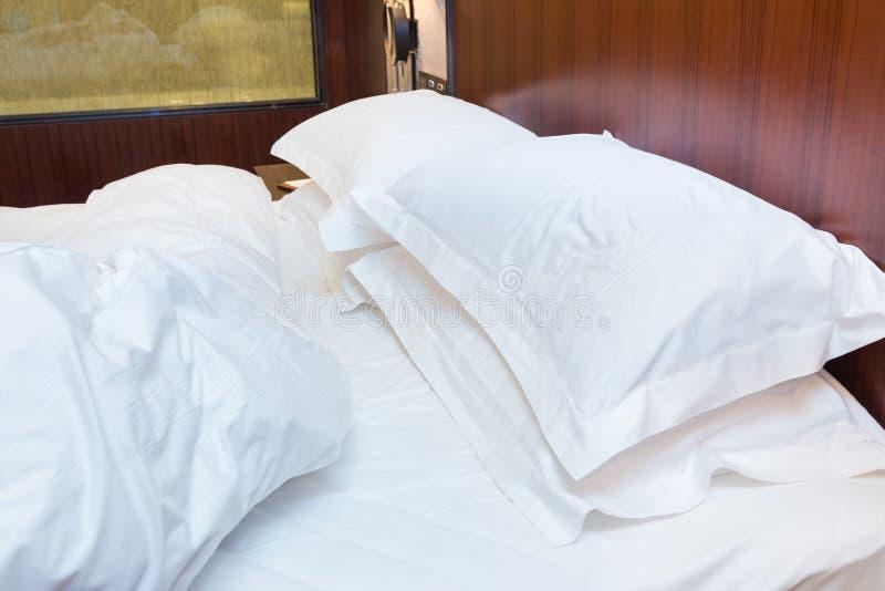 Ogjord säng med det vita arket och kuddar i gammalt sovrum fotografering för bildbyråer