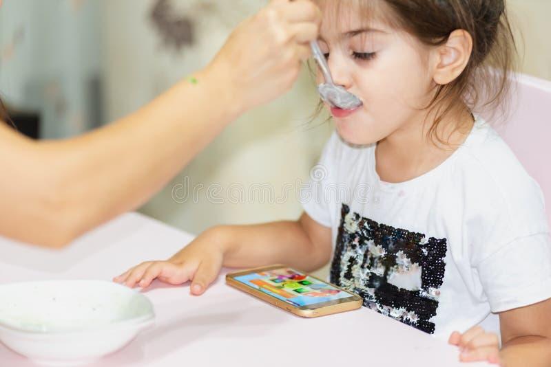 Oglądać mądrze telefon podczas gdy karmiący dziewczyny fotografia stock