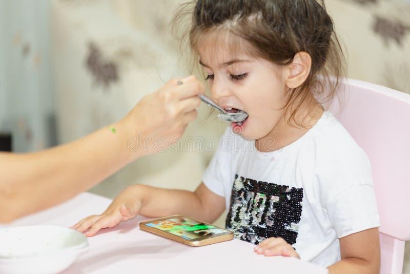Oglądać mądrze telefon podczas gdy karmiący dziewczyny zdjęcie stock