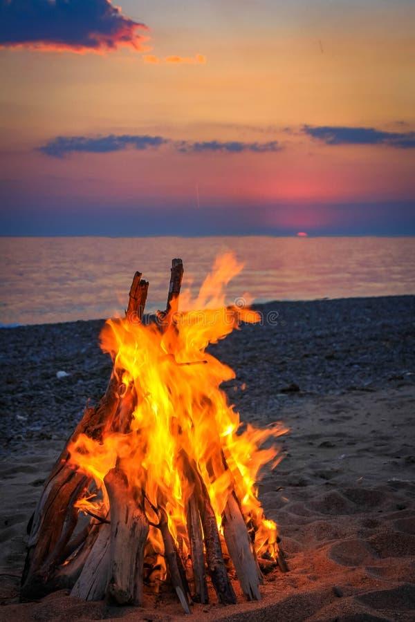 Ognisko na plaży morzem przy zmierzchem fotografia stock