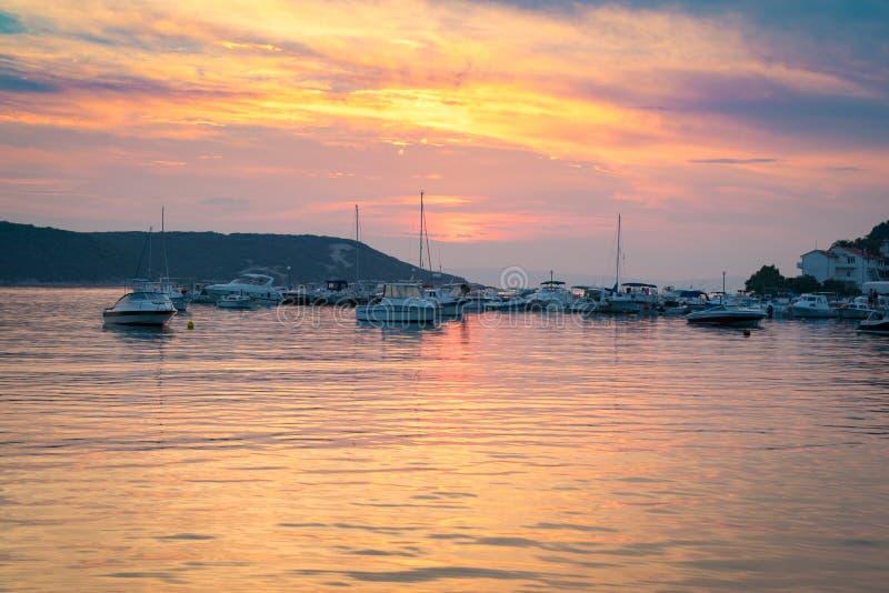 Ognisty zmierzch odbija na morzu mały marina obrazy royalty free