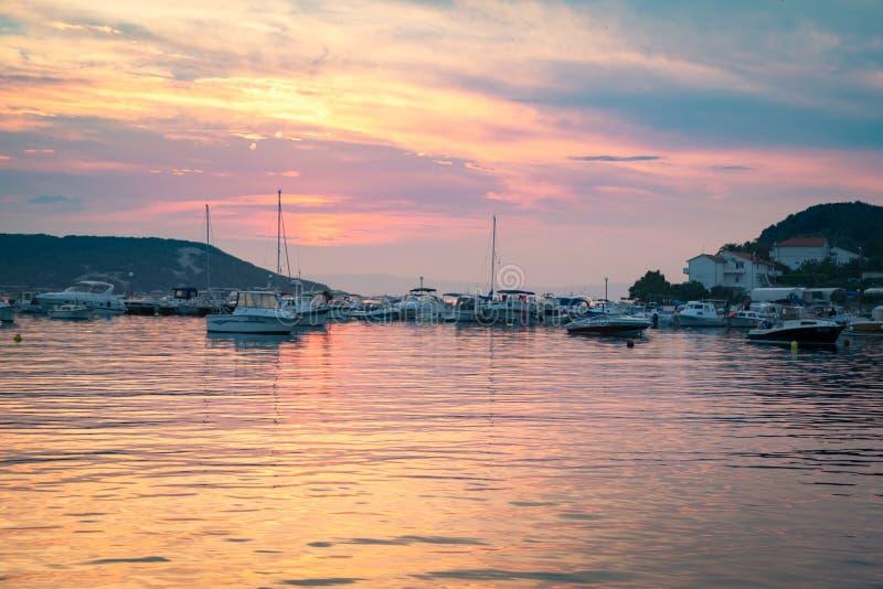 Ognisty zmierzch odbija na morzu mały marina zdjęcia royalty free