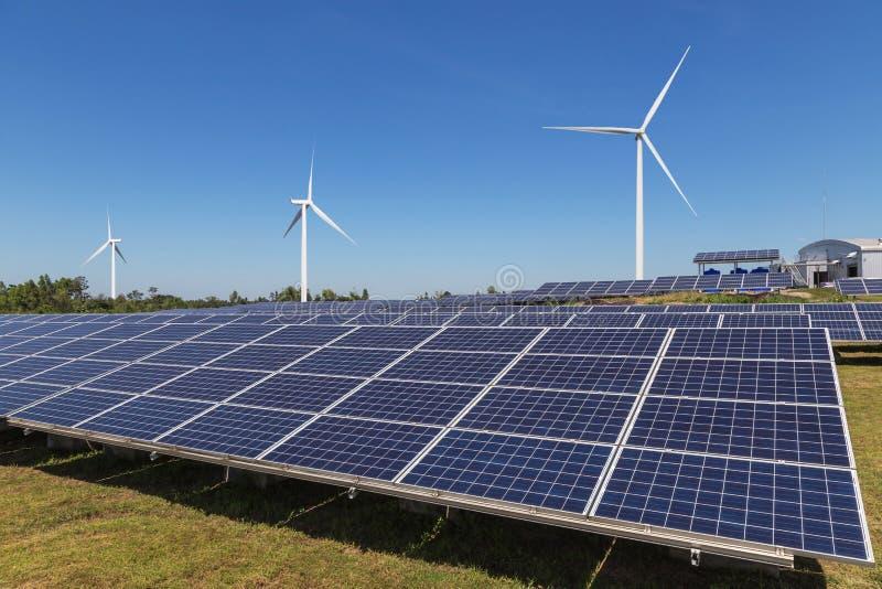 Ogniwa słoneczne z silnikami wiatrowymi wytwarza elektryczność w hybrydowej elektrownia systemów staci na niebieskiego nieba tle zdjęcie royalty free
