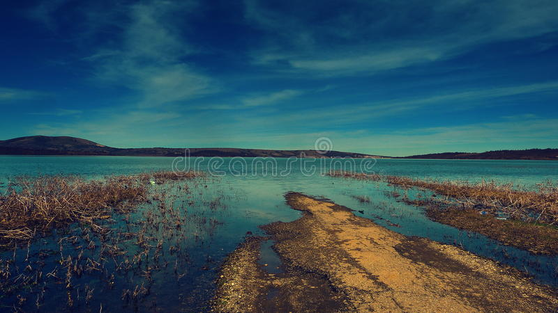 Old road flooded by a lake stock photography