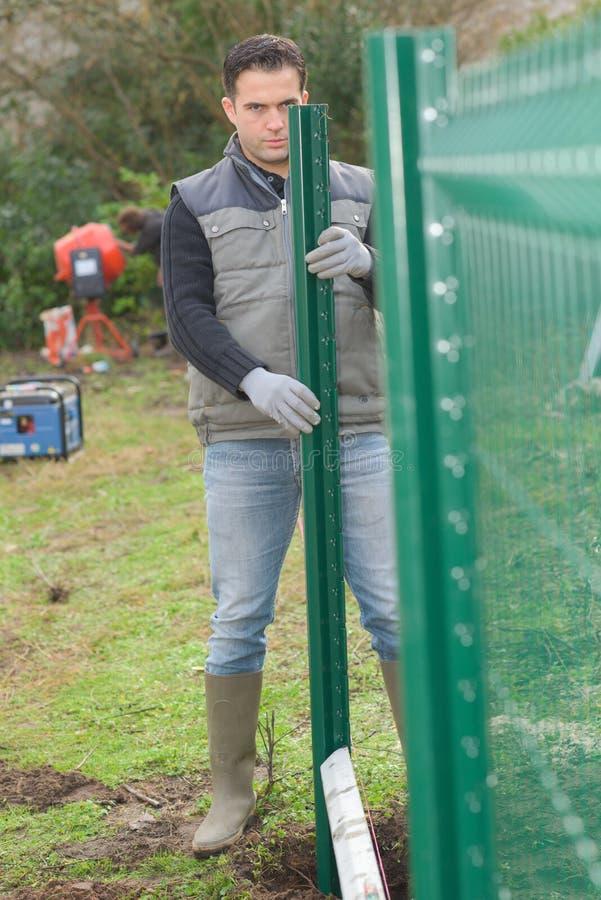 Ogrodniczka instaluje ogrodzenie fotografia royalty free