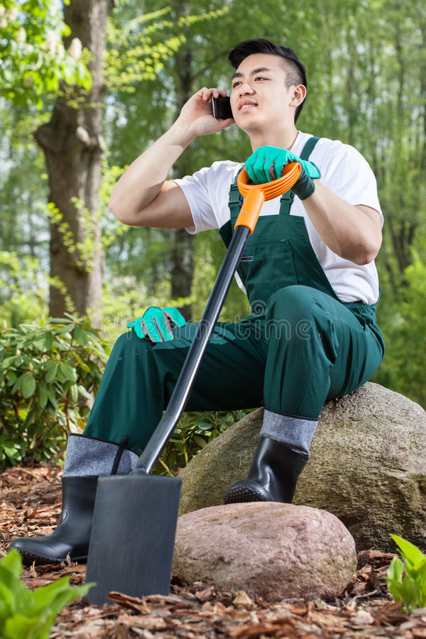 Ogrodniczka odpoczywa, opowiadający na telefonie zdjęcia royalty free