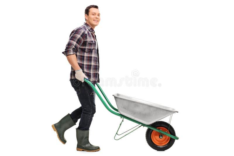 Ogrodniczka pcha pustego wheelbarrow obraz stock