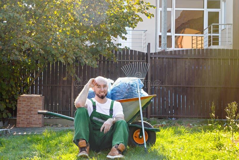 Ogrodniczka w zielonym mundurze jest odpoczynkowa na trawie U?miech i dobry nastr?j Słońce błyszczy na prawej stronie zdjęcie royalty free