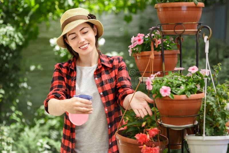 Ogrodniczki dziewczyna z natryskową butelką obraz royalty free