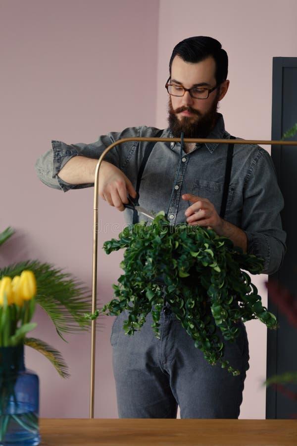 Ogrodniczki tnącej rośliny obwieszenie na złocistym stojaku fotografia stock