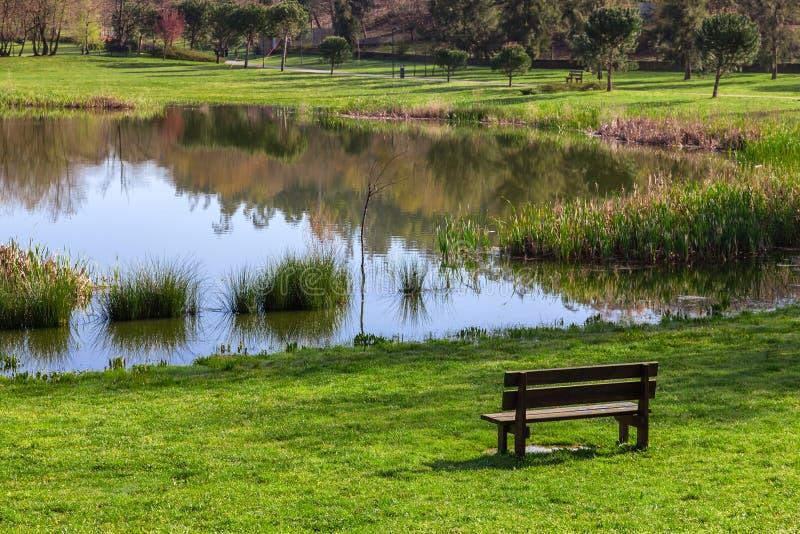 Ogrodowa ławka przegapia staw Parque da Devesa Miastowy park w Vila Nova De Famalicao lub jezioro, Portugalia zdjęcie stock