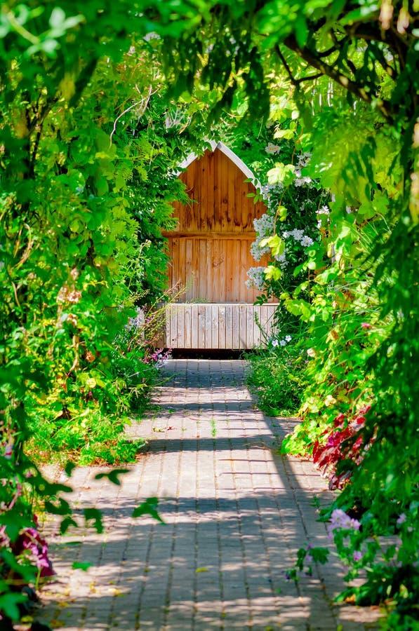 Ogrodowa kryjówka chujący trellis przejścia obsiadania ławki terenu spokojny pusty ocieniony winogradem i różami outdoors zdjęcie stock