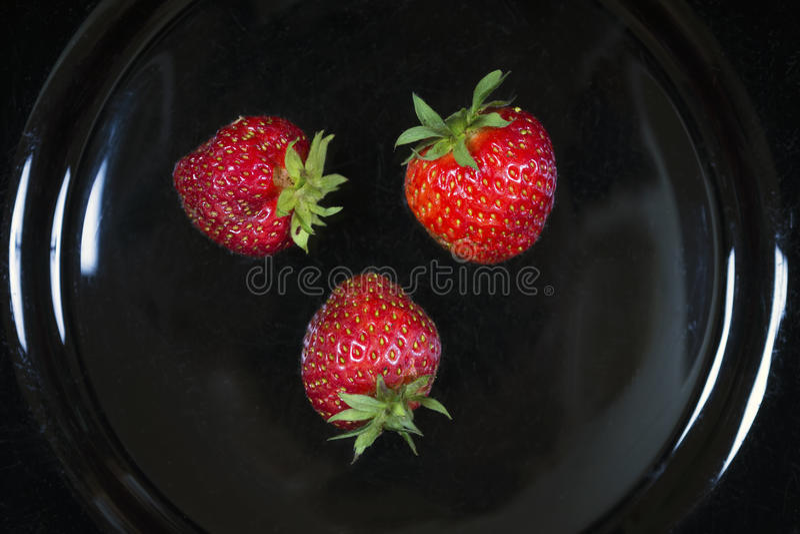 Ogrodowe truskawki na czarnym talerzu obrazy stock