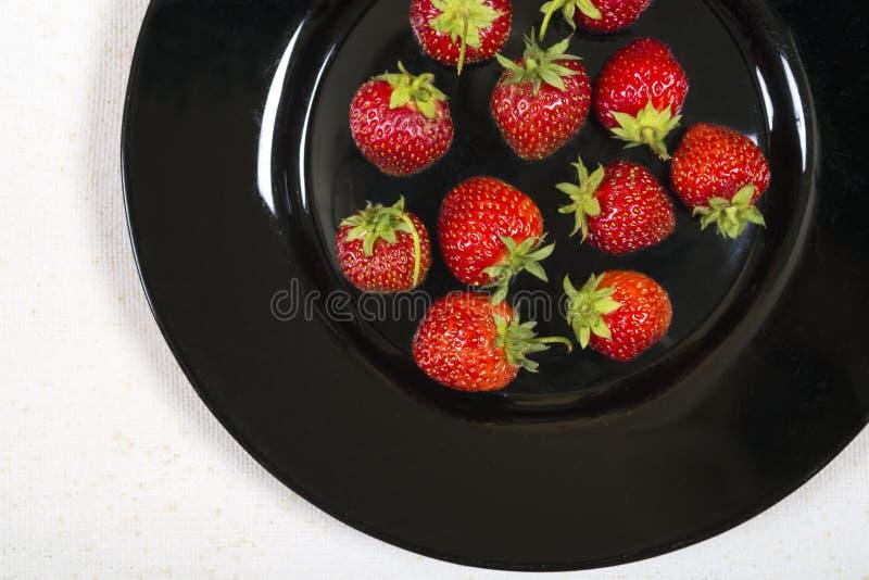 Ogrodowe truskawki na czarnym talerzu zdjęcie royalty free