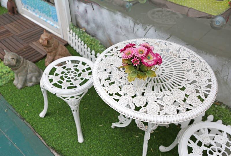 Ogrodowy meble, biel krzesła i stół z kwiatem, obraz stock