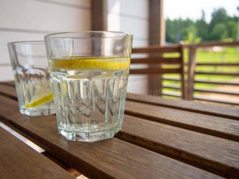 Ogrodowy meble stół i krzesło na tarasie dom na wsi, hotel Dwa szkła z odświeżającym napojem z cytryny zbliżeniem fotografia stock