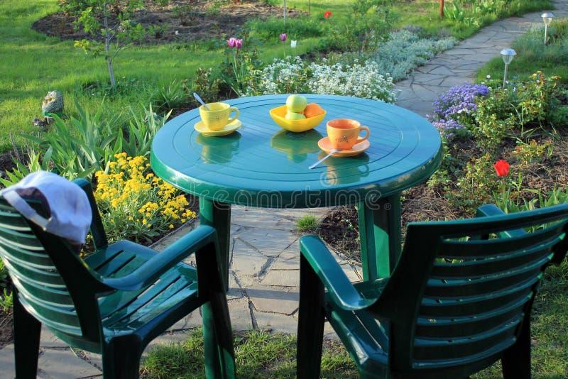 Ogrodowy meble wśród kwiat pobliskiej ogrodowej ścieżki flizy obrazy stock