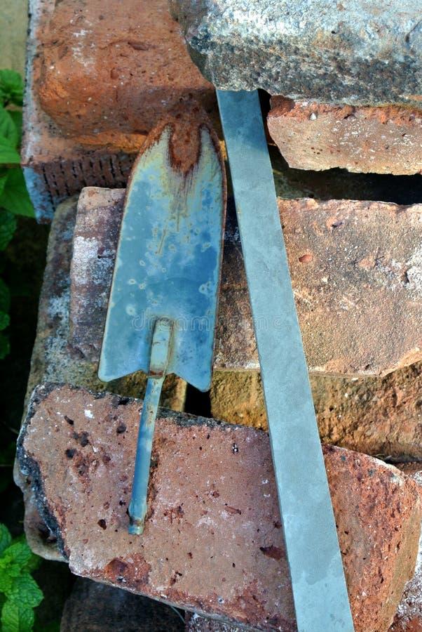 Ogrodowych narzędzi rocznika rydla łopata odpoczywa na antykwarskich cegłach fotografia royalty free
