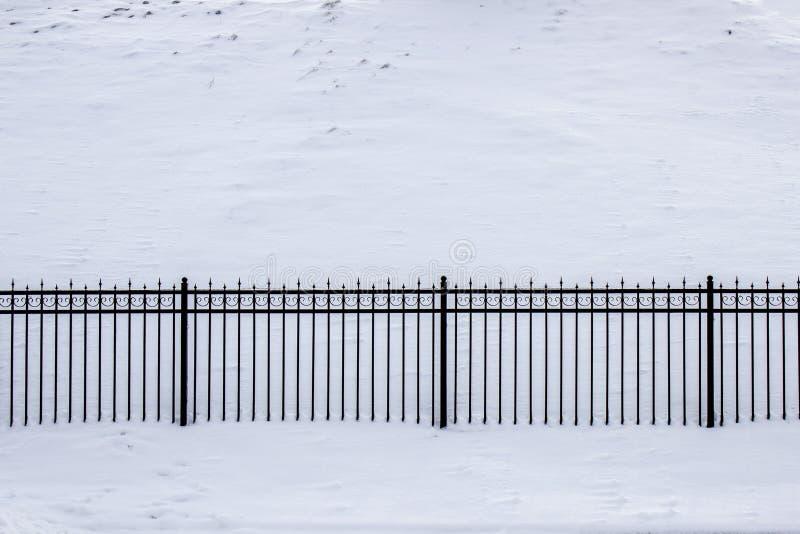 Ogrodzenie robić obsady żelaza kratownicy i granitowe kolumny w chmurnej śnieżnej pogodzie obrazy stock