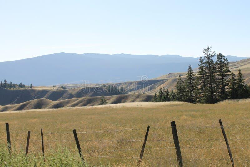 Ogrodzenie w graniach i górkowatych polach obrazy stock