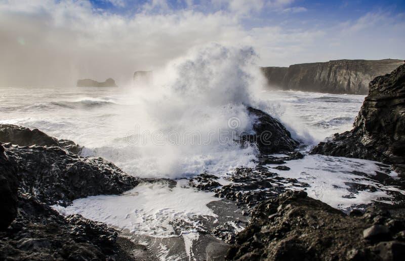 ogromna fala od Atlantyckiego oceanu zakrywa czarnego powulkanicznego kamień na czarnym lawowym piaska banku w Iceland obrazy royalty free