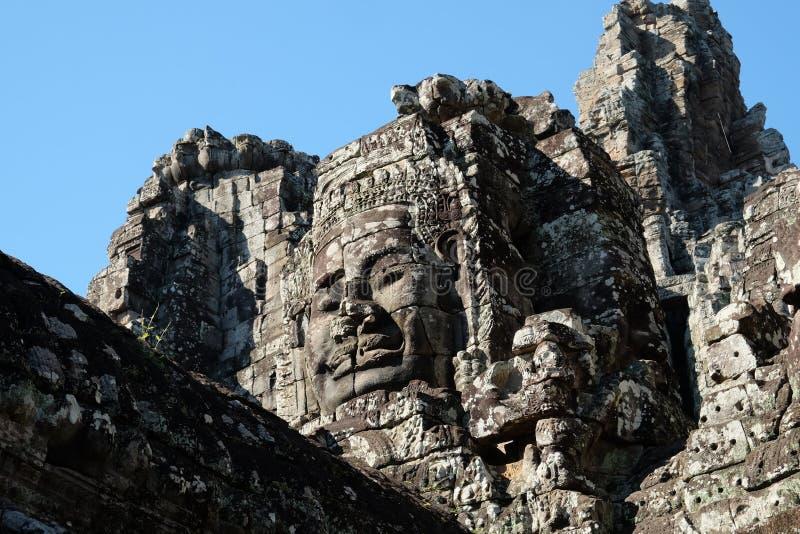 Ogromna twarz ludzka budująca kamienni bloki Ogromne twarze ludzkie na górują Bayon świątynia w Kambodża Architektoniczna sztuka zdjęcia royalty free