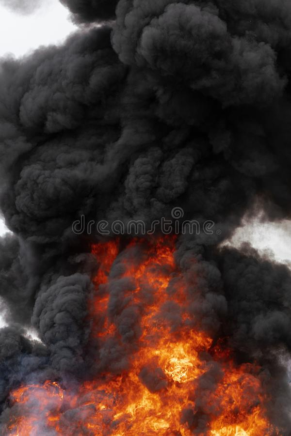 Ogromni p?omienie rudopomara?czowy ogie?, ruchu zmroku dym chmury zakrywali niebo zdjęcie royalty free
