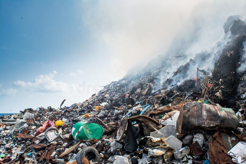 Ogromny śmieciarskiego usypu terenu widok pełno dym, ściółka, klingeryt butelki, banialuki i inny grat przy Thilafushi wyspą, zdjęcia royalty free