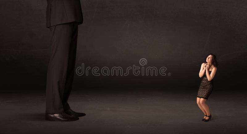Ogromny mężczyzna z małą bizneswoman pozycją przy frontowym pojęciem obraz royalty free
