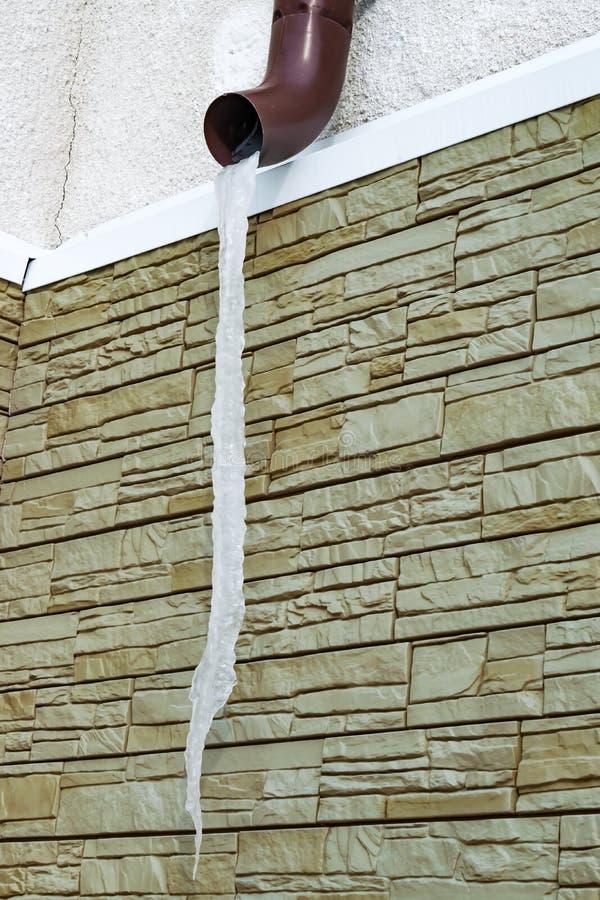Ogromny sopel w wiośnie przeciw ścianie budynek, wiosna fotografia royalty free