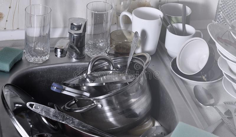 Ogromny stos nieumyci naczynia w kuchennym zlew na countertop i Mnóstwo kuchenni urządzenia przed myć i naczynia fotografia stock