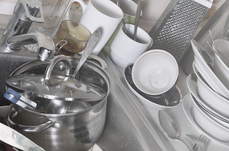 Ogromny stos nieumyci naczynia w kuchennym zlew na countertop i Mnóstwo kuchenni urządzenia przed myć i naczynia obraz stock