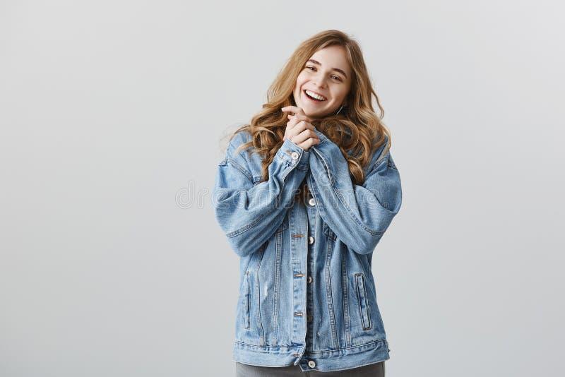 Oh, оно настолько милый, я касано Портрет довольной женственной городской девушки в стильной куртке джинсовой ткани, держа обхвач стоковая фотография