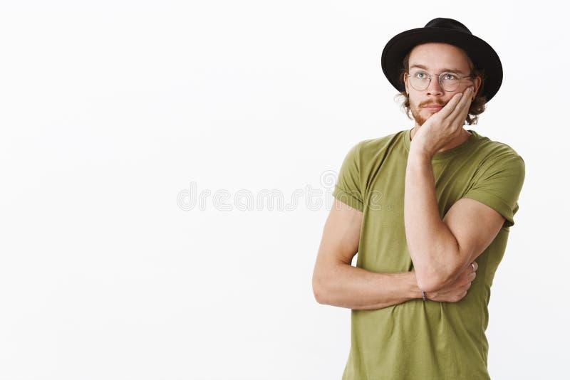 Oh deus porque mim Retrato do desenhista masculino criativo novo intenso, irritado e incomodado com barba, vidros e chapéu fotografia de stock