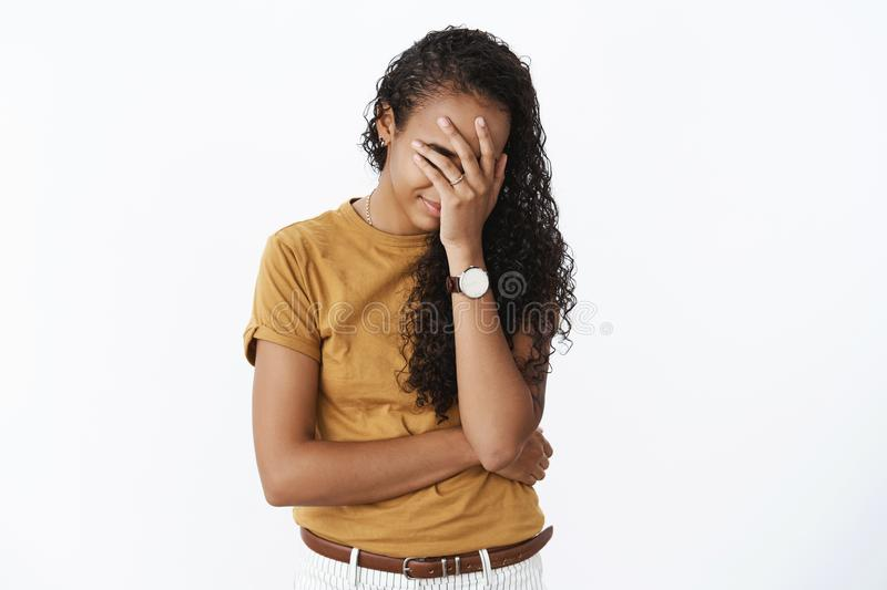 Oh gosh please stop. Portrait of embarrassed awkward cute african-american girlfriend with long curly hair bending. Making facepalm gesture as being humiliated royalty free stock image