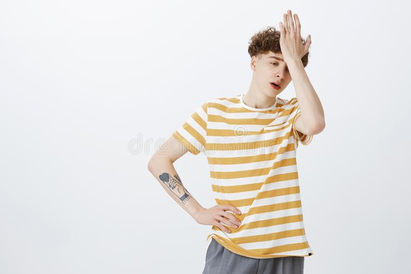 Oh gosh porque mim Retrato do adolescente novo incomodado e acima alimentado inquieto com penteado encaracolado e da tatuagem na  fotos de stock