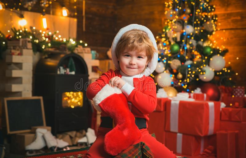 Oh happy day. Child cheerful face got gift in christmas sock. Contents of christmas stocking. Joy and happiness. Childhood moments. Kid boy santa hold stock photography