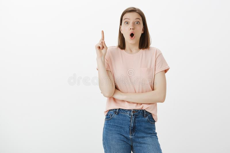 Oh j'ai l'idée Portrait de jeune femme européenne attirante enthousiaste dans le T-shirt et des jeans roses, soulevant l'index de photos libres de droits