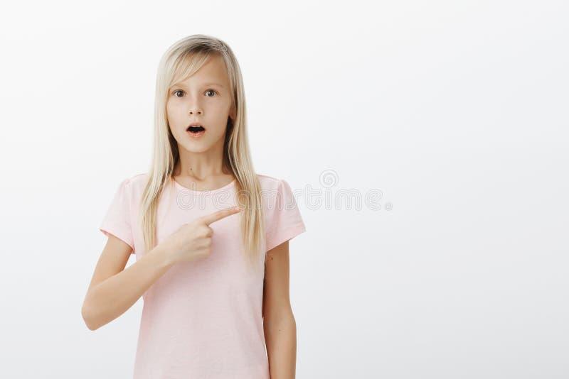 Oh mon ça alors vous avez vu Portrait de petite fille blonde stunned stupéfaite dans le T-shirt rose, se dirigeant juste avec la  photos libres de droits