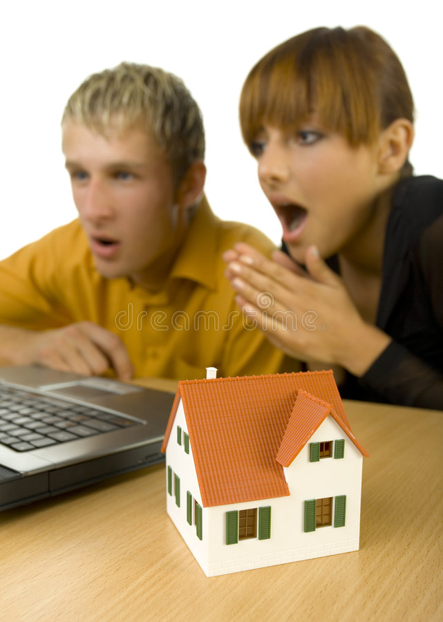 Oh my god!. Young couple sitting at desk in front of computer. They are looking surprised. House miniature is standing on desk. Focus on little house. White royalty free stock photography