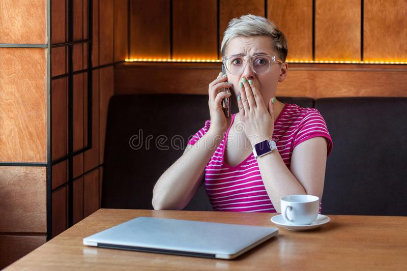 Oh my God! Portrait of unbelievable shocked young bussineswoman with short hair in pink t-shirt and eyeglasses is sitting in cafe stock images