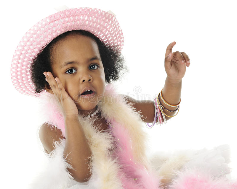 Oh My! Says this Tiny Diva. Close-up image of an adorable 2 year old diva in beads, boas and bangles. She's looking at the viewer with one hand on her cheek. On stock photos