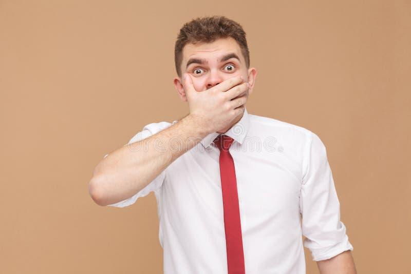 Oh não! Homem com a boca fechado da mão dos olhos grandes fotografia de stock