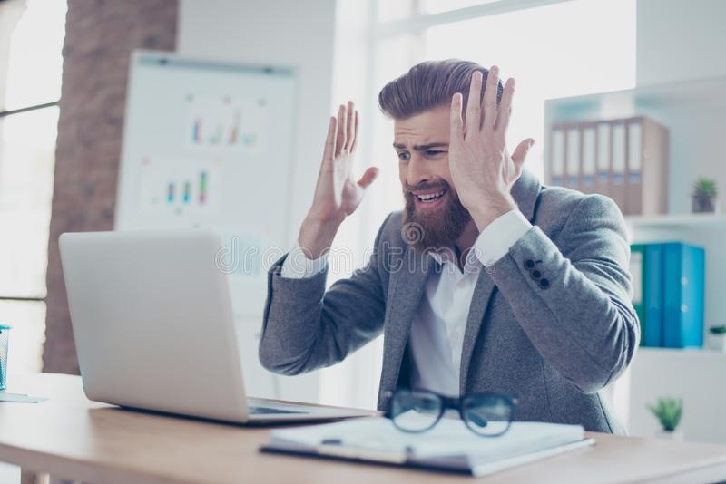 Oh no! Frustrated young businessman screaming because of finding. A mistake in his counting, in a formal wear sitting at the office royalty free stock photography