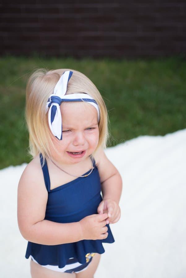 Oh no Niño infeliz de la muchacha con el pelo rubio Pequeño griterío de la muchacha al aire libre Venda elegante del pequeño desg fotografía de archivo