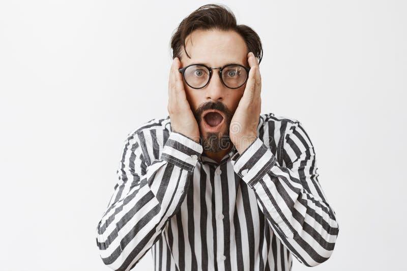 Oh no plazo cerca Retrato del hombre maduro nervioso chocado con la barba y del bigote en vidrios y camisa rayada fotografía de archivo libre de regalías