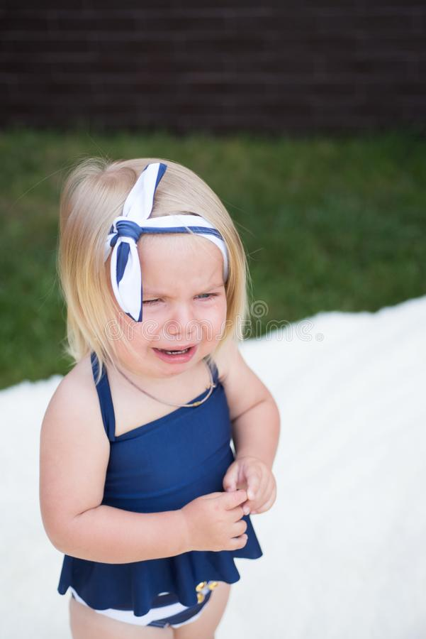Oh no. Unhappy girl child with blond hair. Small girl crying outdoor. Small child wear stylish headband in hair. Hair stock photography