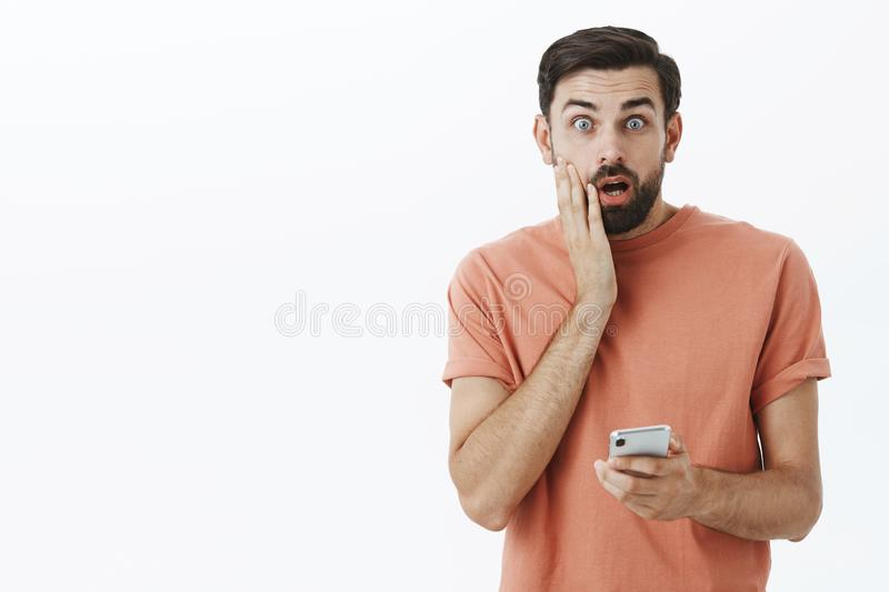 Oh no, wrong number. Portrait of man accidently sent message via smartphone wrong person touching face and open mouth stock photography