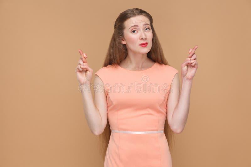 Oh per favore donna promettente con le dita attraversate che esaminano macchina fotografica fotografia stock