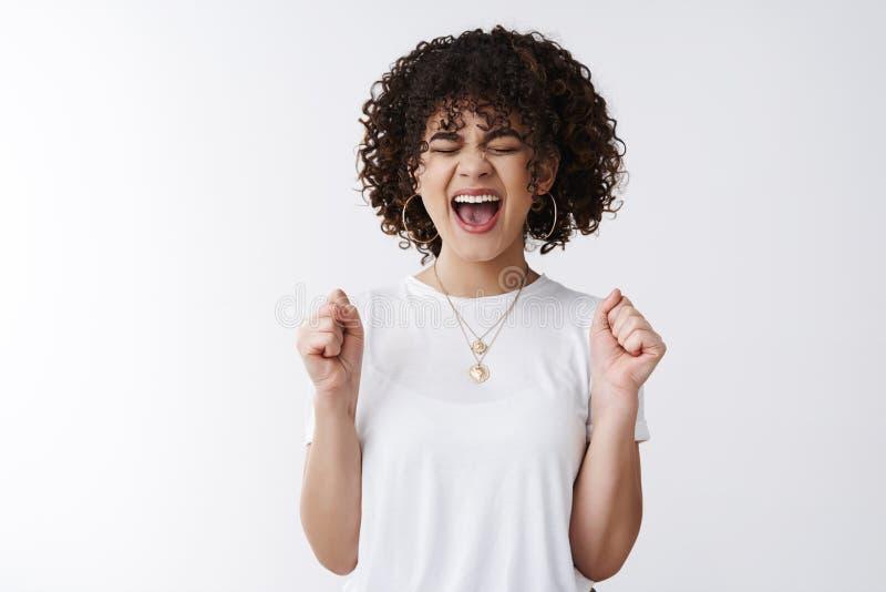 Oh sì sì Grido di conquista riuscito riccio-dai capelli sveglio di trionfo felice emozionante della ragazza che incoraggia felice fotografie stock libere da diritti